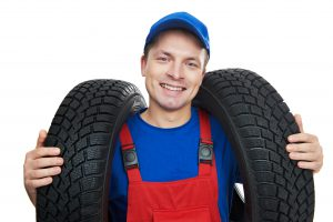 Serviceman repairman automobile mechanic with two car tyres isolated