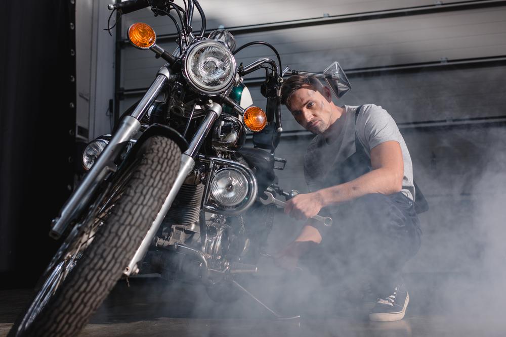 Mechanik opravujúci motorku v garáži