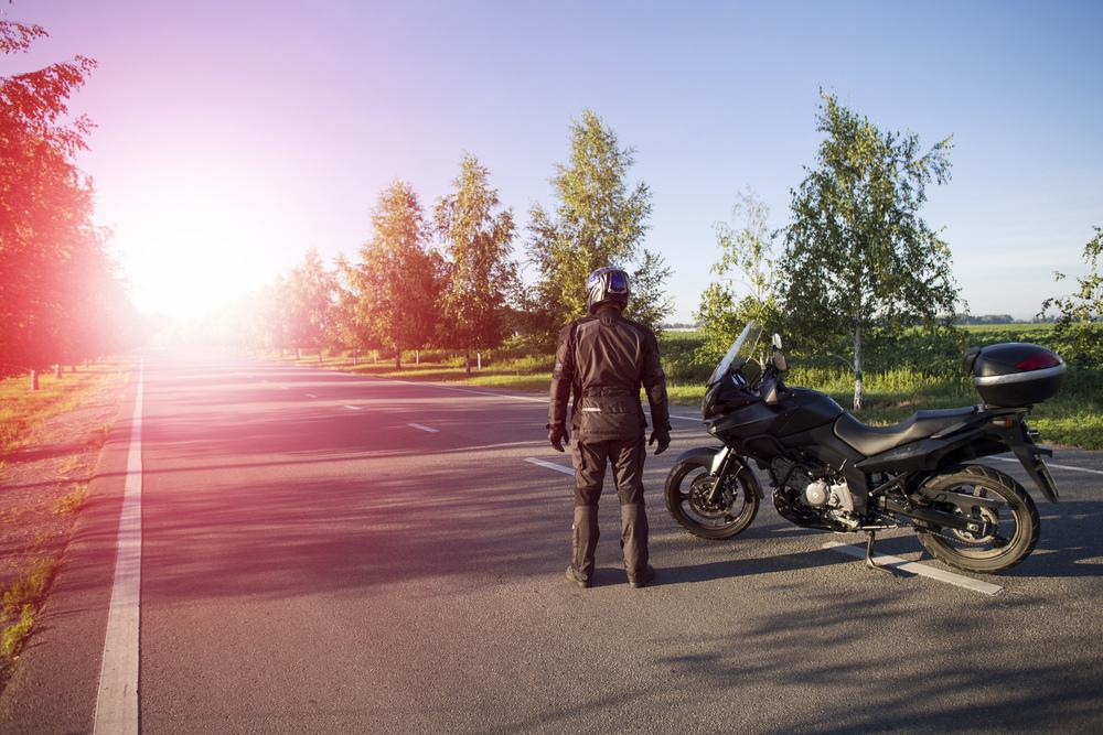 Muž v motorkárskom oblečení s motorkou