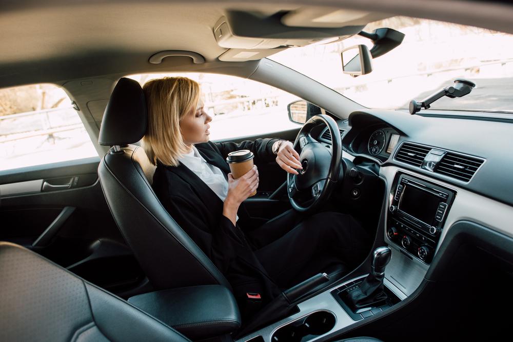 Žena za volantom s kávou v ruke
