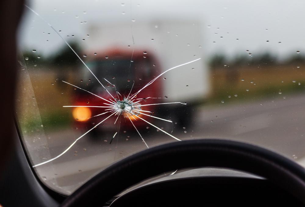 Predné sklo auta s prasklinou z pohľadu vodiča
