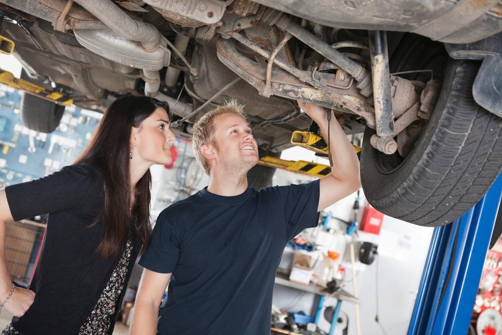 Muž so ženou obzerajú zospodu nápravu auta