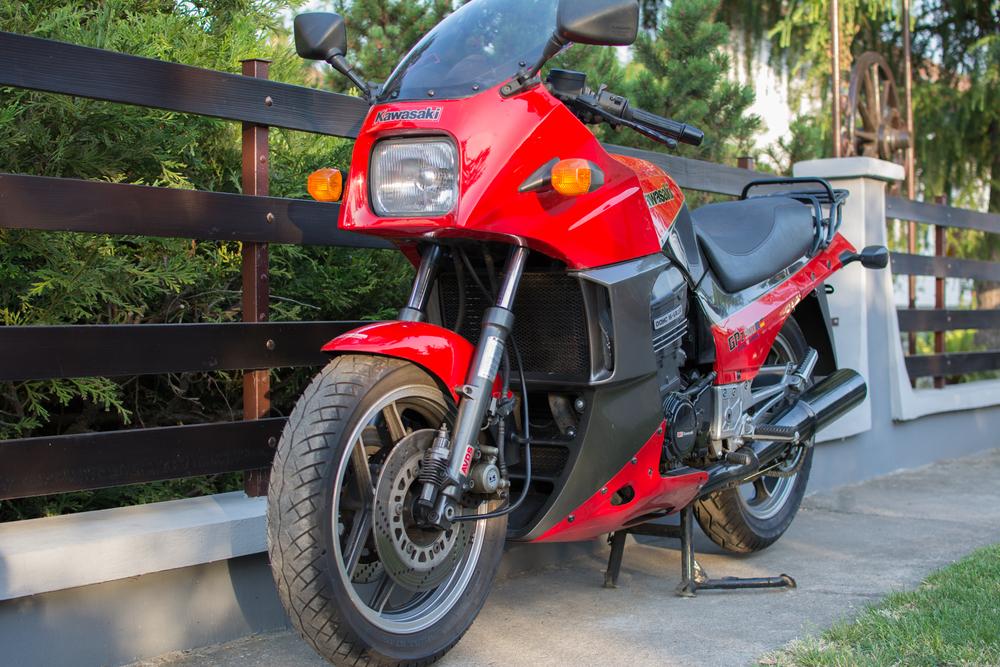Červená motorka pri plote