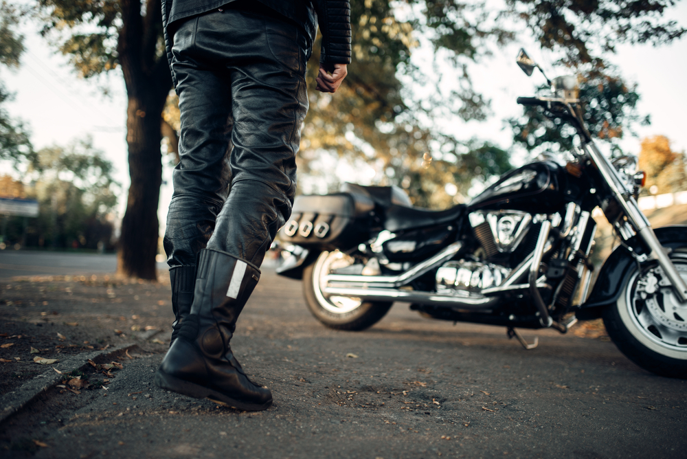 Čierna motocyklová obuv, nohavice a motorka v pozadí