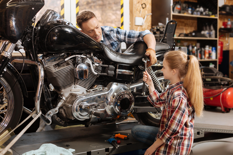 Muž s dcérou opravujú motorku v domácej dielni