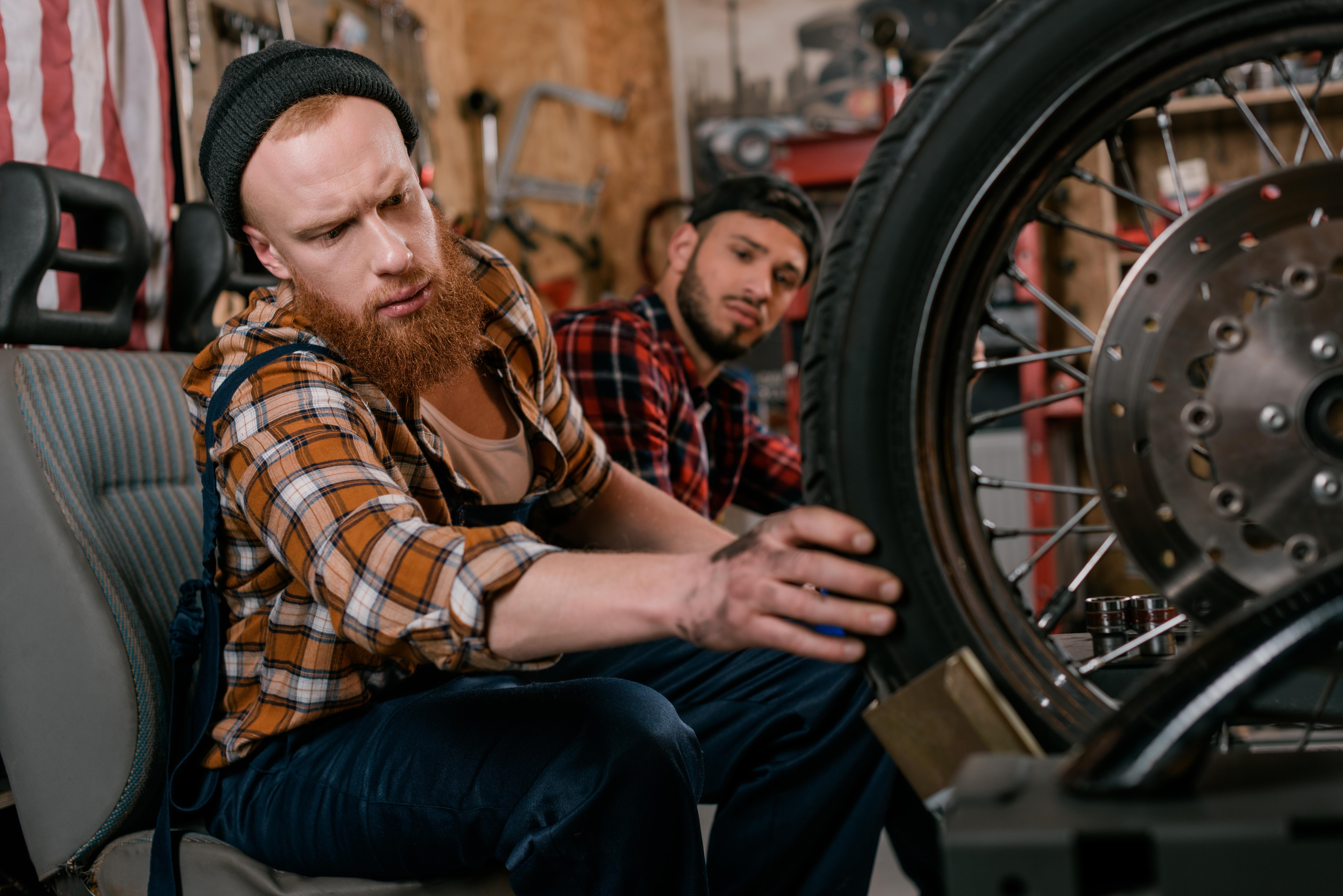 Mladí muži si prezerajú pneumatiku na motorke