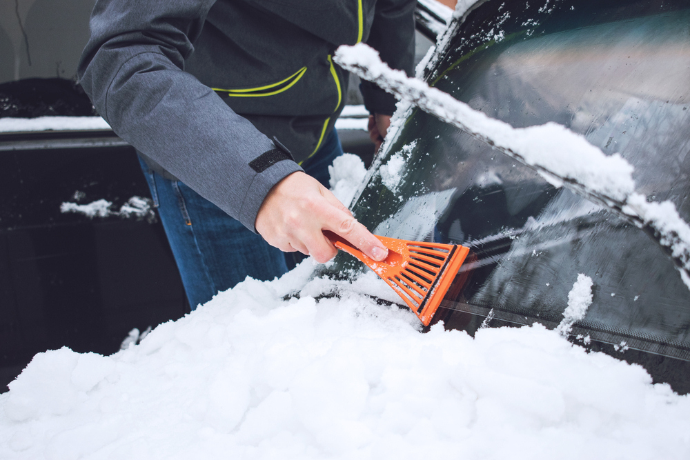 Muž zoškrabuje sneh a ľad zo skla auta