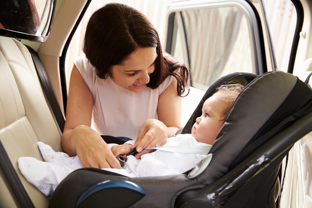 Žena upína dieťa v autosedačke